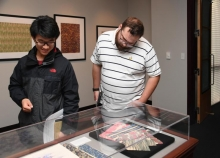 Papermaking Museum: RBI Fellows Xirui Peng, ME, and Daniel Kimmel view papers on display during the opening of 'Marvelous Marbling: Demystifying Marbled Papers'